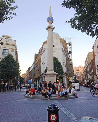 Seven Dials sundial pillar after cleaning, being enjoyed as a meeting place