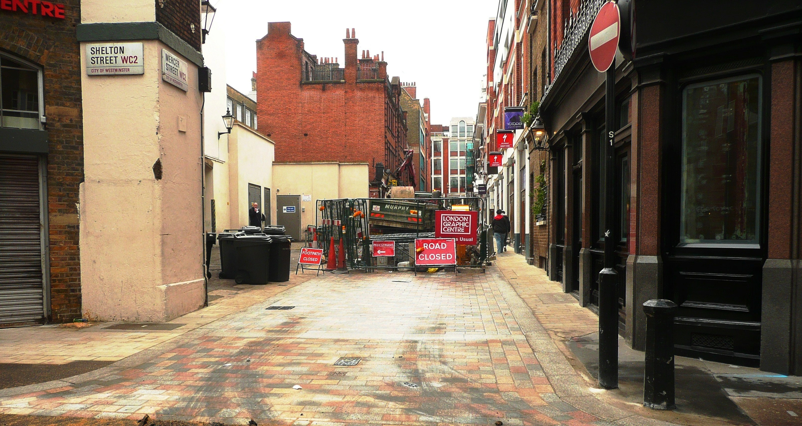 Westminster City Council's works, laying multi-coloured dressed setts in Mercer Street South.